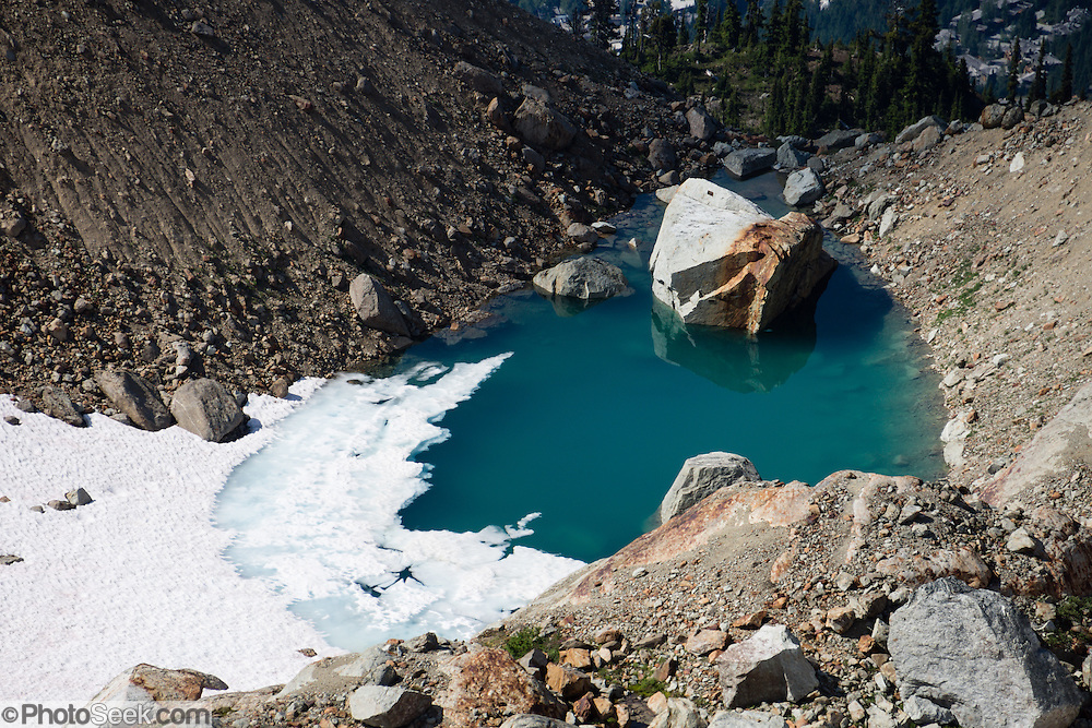 View a snow enrusted alpine lake from atop Whistler Peak in the Coast Range, British Columbia, Canada.