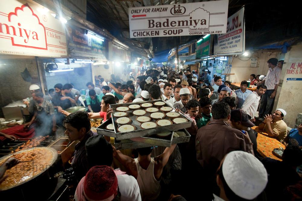 """A man carries """"Firni"""" a sweet dish through a crowded lane by Bade Miyan Chicken Soup stall at the enterance of Minara masjid at Mohammed Ali road in Mumbai, Maharashtra, India, on Saturday September 6, 2009. Photographer: Prashanth Vishwanathan/The National"""