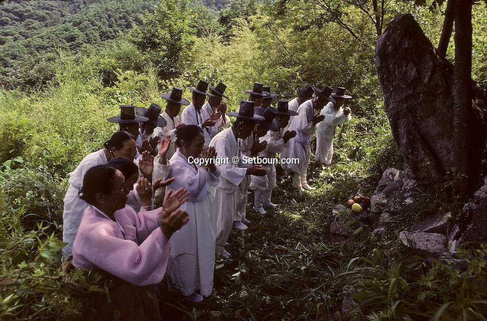 """Chonhakdong traditional confucianist village. at  the occasion of """"tano"""" (equivalent for occidental traditional harvest feasts) the elders honour one of their holy places. They have to spend hours in train or bus to reach the holy mountain.  //////On their way back to the village, a group has stopped in :front of the house where the founder has taught. Prayers and gifts ceremony.      Korea   village traditionnel confucianiste de Chonhakdong //////A l'occasion de Tano (difficile à traduire mais l'equivalent de nos anciennes fêtes des moissons, les anciens du village vont honorer un de leurs lieux sacres. Il faudra des heures de train et de bus avant de rejoindre la montagne sacree.    Coree   Sur le chemin du retour, le petit groupe s'arrête devant ce qui reste des bâtiments où le maître a enseigne, le temps d'une prière et d'une ceremonie d'offrandes.    Coree  //////R28/54    L2671  /  R00028  /  P0003048"""