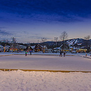 Ice skating at North Conway's Schouler Park with Cranmore Mountain in the distance.