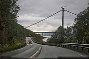 Bygging av Hålogalandsbrua utenfor Narvik i Nordland. Den skal krysse Rombaken mellom Karistranda, 2,2 kilometer nordøst for Narvik sentrum, og Øyjord, ti kilometer sør for Bjerkvik. <br /> Brua blir en del av E6, og forkorter strekningen fra Narvik til Bjerkvik med 18 kilometer, og fra Narvik til Bjørnfjell med 4-5 kilometer. Brua vil også avhjelpe vektbegrensinger på den eksisterende Rombaksbrua, og gi en mer rassikker forbindelse enn dagens E6. Dette har ført til at Narvik lufthavn, Framnes ble lagt ned 1. april 2017. Reisende blir henvist til Harstad/Narvik lufthavn, Evenes, i det kjøretiden til Evenes med bru, kortes ned fra ca. 60 til 40 minutter (fra 75 til 57 km). <br /> Hålogalandsbrua blir 1533 meter lang, med et fritt spenn på 1145 meter og blir med det Norges nest lengste hengebru etter Hardangerbrua. På grunn av stor forskjell i kostnad mellom de forskjellige alternativene til brukonstruksjon, bestemte Statens vegvesen våren 2008 at bare hengebru skal vurderes i den videre prosjekteringen. Statens vegvesen (2008) kostnadsberegnet prosjektet til 1860 millioner kroner, inkludert tilknytningsveier og -tunneler.<br /> Bruprosjektet drives av Hålogalandsbrua AS, der Narvik kommune er majoritetseier med 75,95% av aksjene. Prosjektet er inne i Regjeringens forslag til Nasjonal transportplan for perioden 2010 til 2019, og det er foreslått lagt til første del av planperioden. I mai 2012 kunngjorde Samferdselsminister Magnhild Meltveit Kleppa at finansieringen for prosjektet er på plass.<br /> Byggestart var 18. februar 2013. I sammenheng med brobyggingen, ble rassikringstunnelen Trældaltunnelen åpnet den 11. september 2015. Brua vil etter planene åpnes for trafikk sommeren 2018. Norsk bru blir kinesisk stålindustris inngangsbillett til Europa. <br /> Et kinesisk stålverk har vunnet konkurransen om å levere det meste av metallet til den nye Hålogalandsbrua i Narvik, som skal stå ferdig neste sommer.<br /> Hålogalandsbrua<br /> Foto: Statens vegvesen<br /> Kinas s