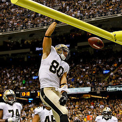 September 23, 2012; New Orleans, LA, USA; New Orleans Saints tight end Jimmy Graham (80) dunks over the goal post after scoring a touchdown against the Kansas City Chiefs  during the third quarter of a game at the Mercedes-Benz Superdome. The Chiefs defeated the Saints 27-24 in overtime. Mandatory Credit: Derick E. Hingle-USA TODAY SPORTS