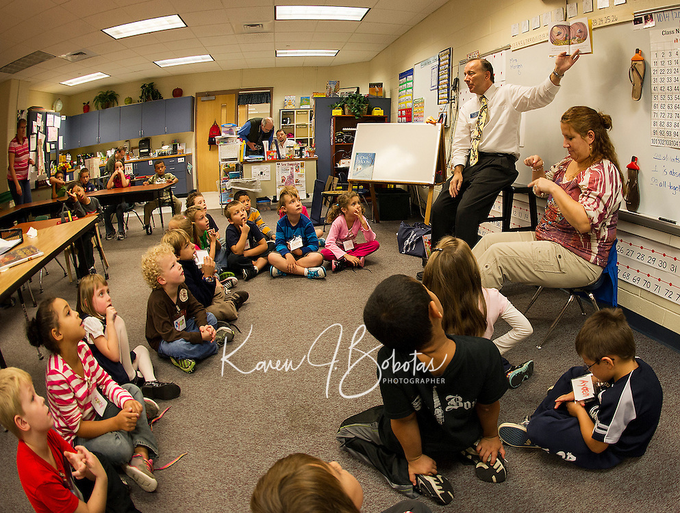 "Participating in the ""Read for the Record"" early childhood literacy campaign LRCC President Dr. Scott Kalicki reads ""There was an Old Lady who Swallowed Fly Guy"" as Mrs. Chase uses sign language for the first grade students in Mrs. Faria's and Mrs. Olson's classrooms at Pleasant Street School Thursday afternoon.  (Karen Bobotas/for the Laconia Daily Sun)"