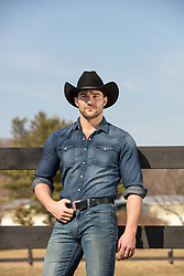 masculine cowboy by a fence