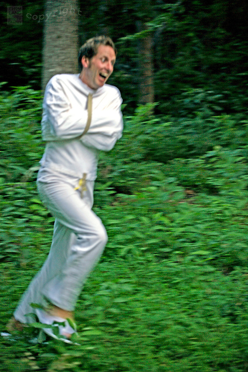 A man with a crazed look and wearing a straitjacket runs through the woods.