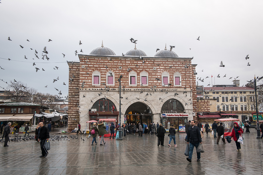 The exterior of the Istanbul Spice bazaar in Turkey on a rainy day as shoppers go in and out with pigeons soaring in the air.