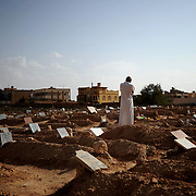 A brother of a rebel martyr contemplates the grave of his sibling at Zintan's graveyard.