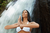 Young woman meditating by waterfall low angle view
