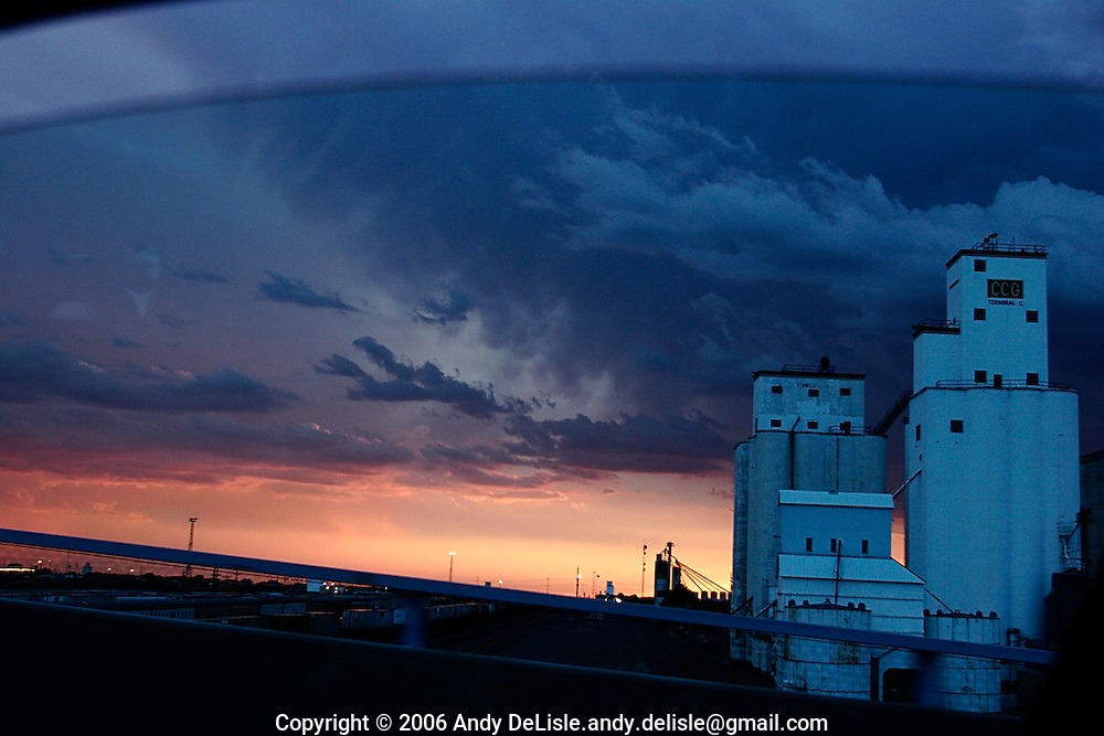 The sun sets on a partly cloudy evening behind the Peavey Grain Elevators as seen from the Prince Street overpass in Clovis, NM.