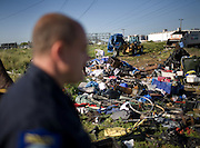Sacramento police officer Mike Cooper watches as city crews clean up the left behind belongings of the homeless after they were moved from a tent city in Sacramento, CA.
