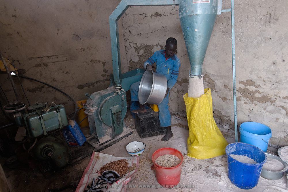A young operator at work in a sorghum mill in the village of Kudo in Eastern Equatoria in South Sudan on 8 August 2014.