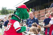 Picture by David Horn/Focus Images Ltd. 07545 970036.04/08/12.Arsenal mascot, Gunnersaurus, signs autographs for young Chesham United fans before a friendly match at The Meadow, Chesham.