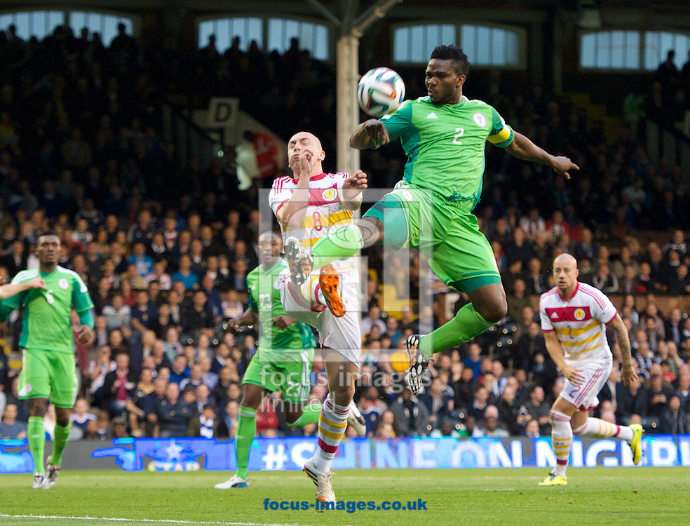 Peter Odemwingie of Nigeria takes a high ball in front of Scott Brown of Scotland during the International Friendly match at Craven Cottage, London<br /> Picture by Alan Stanford/Focus Images Ltd +44 7915 056117<br /> 28/05/2014