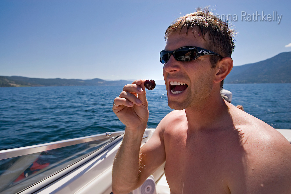 Man eats a cherry on the speed boat on a sunny summer day on Okanagan Lake, BC Canada.