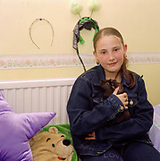 A young teenage girl holding her pet guinea pig in her bedroom, Cardiff, UK 2000's