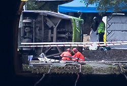 © Licensed to London News Pictures. 09/11/2016. London, UK. Members of an investigation team inspect the underside of a tram (pictured left) which derailed near Sandilands tram station in Croydon, Greater London. Dozens of people are believed to be injured with emergency services saying that there has been a number of fatalities . Photo credit: Peter Macdiarmid/LNP
