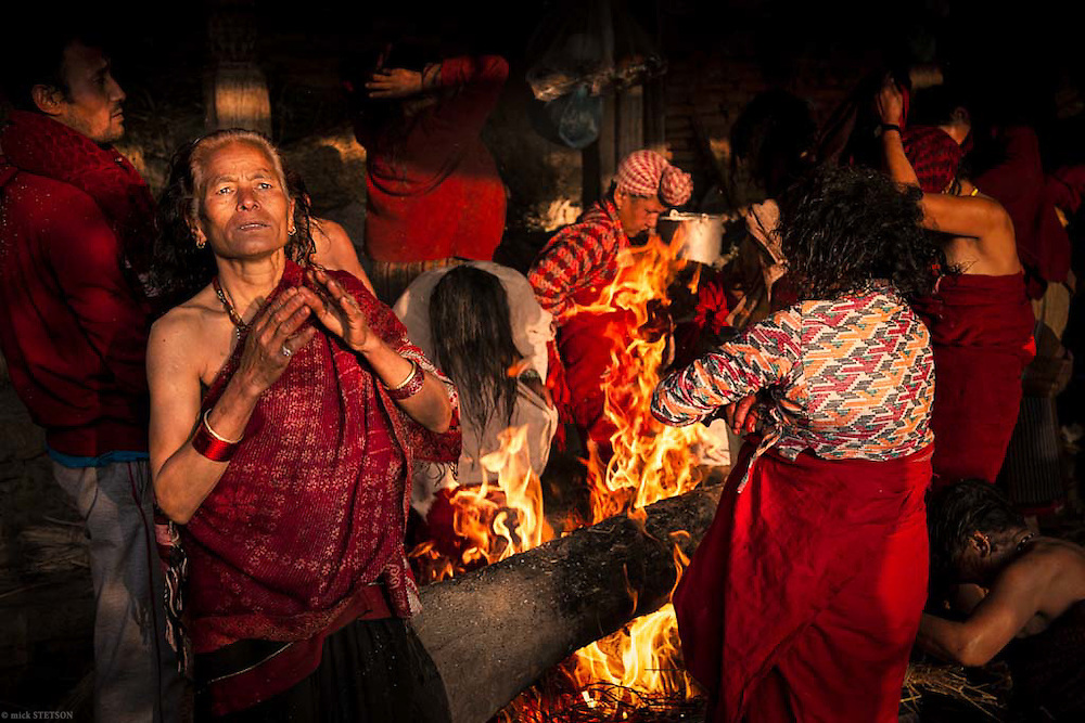 — After finishing their ritual bath and offering prayers to the gods, the devotees crowd a fire prepared by the men attendants. According to ancient Hindu texts the god of fire, Agni, is conceptualized as existing on three levels: on earth as fire, in the atmosphere as lightning, and in the sky as the sun.  Agni is considered the mouth of the gods.