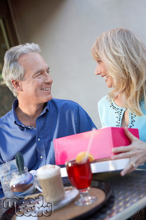 Couple sitting at cafe table on Shopping Trip wife opening gift