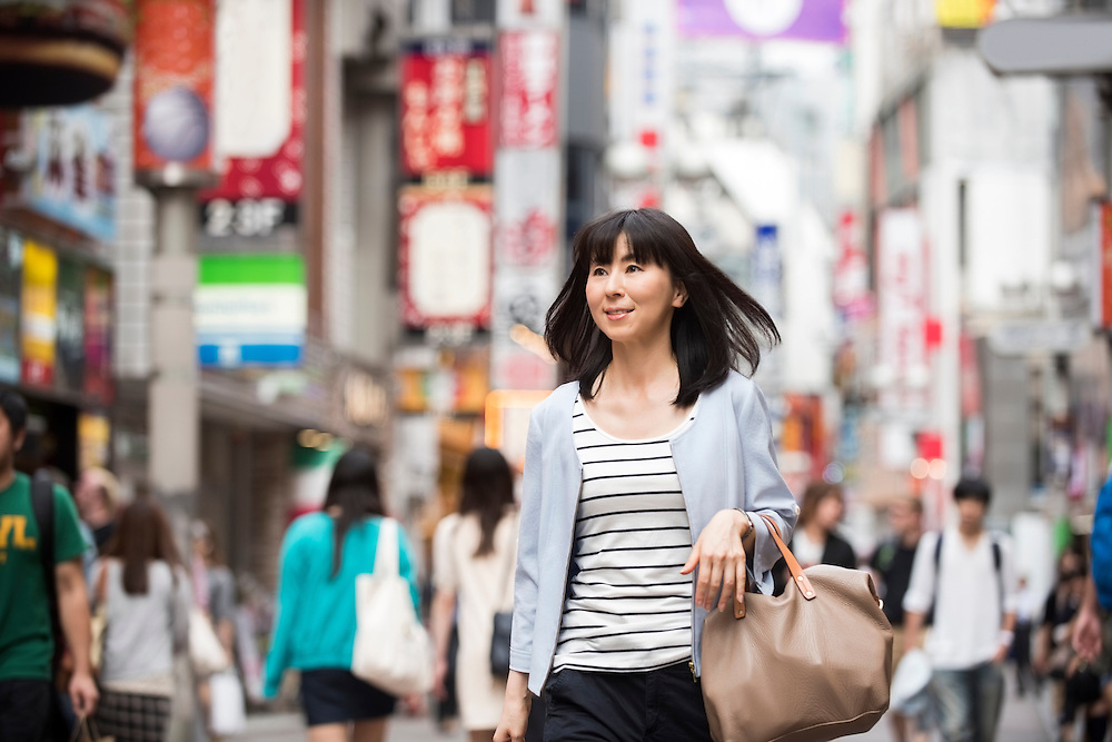 Candid portrait of mid adult Japanese woman walking through streets of Shibuya, Tokyo, Japan. Asian female in her 30's out shopping in urban shopping district.