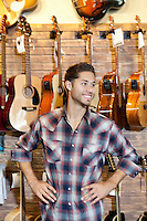 Happy young music store owner with hands on hips standing in front of guitars