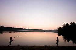 Two kids fishing as the sun sets over Otter Lake in Greenfield State Park in Greenfield, New Hampshire.
