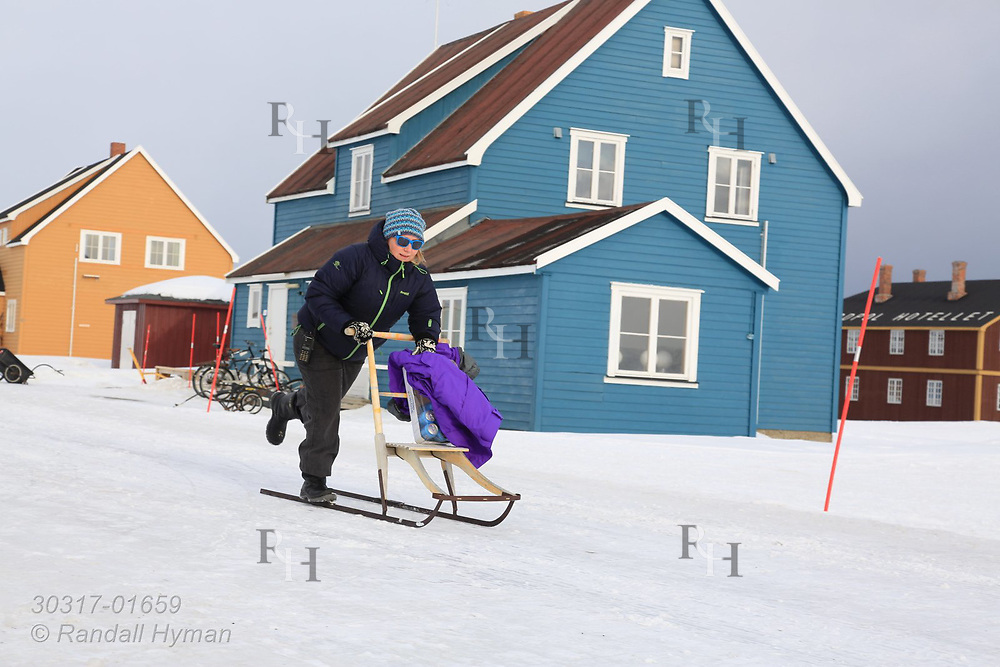 "Woman on kicksled, or ""spark,"" glides along snowy road at the international science village of Ny-Alesund on Spitsbergen island in Kongsfjorden; Svalbard, Norway."