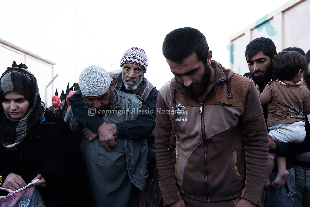 Iraq: as they arrive by truck a man carries an old man<br /> at the entrance of the Hasan Shame IDP camp in Al Kazir area after fleeing fighting in Mosul on November 5, 2016. Alessio Romenzi