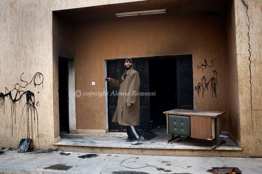 A Libyan man gestures as he walks in a burnt down police station in Benghazi, Libya on February 25, 2011..ALESSIO ROMENZI