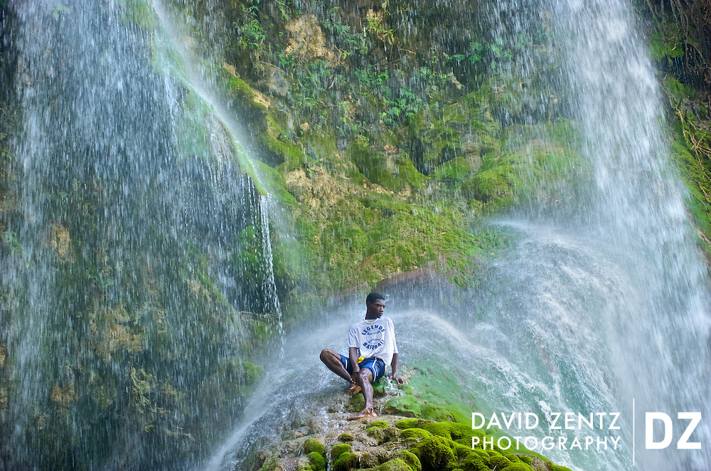 A young pilgrim sits beneath the falls of Saut D'eau in central Haiti during the annual 3-day voodoo festival held there on July 15, 2008.