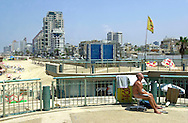 An Israeli resident sunbathes nude on a porch overlooking Chinky beach on the Mediterranean coast of Tel Aviv Thursday Aug. 2, 2001. Despite the 11 months of violence Israelis and Palestinians take a break to enjoy the mediterrenean beaches and the Dead Sea, where under growing tensions and in the case of Gaza under closure people try to  make the best of their summer and carry on a normal life. (AP PHOTO/Elizabeth Dalziel)