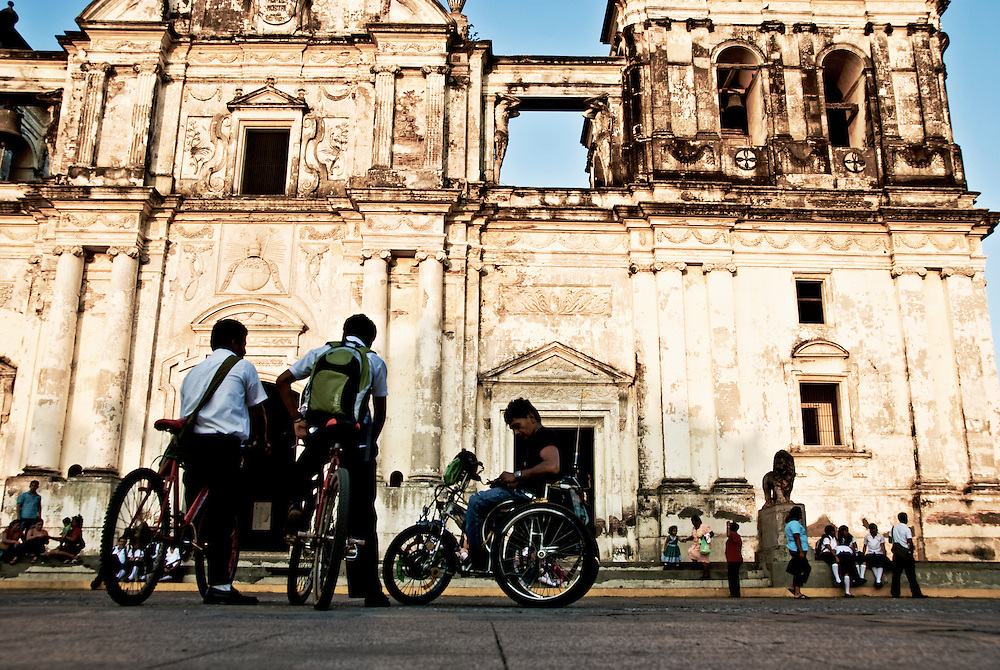 A congregation of boys on wheels in front of the Leon Cathedral.