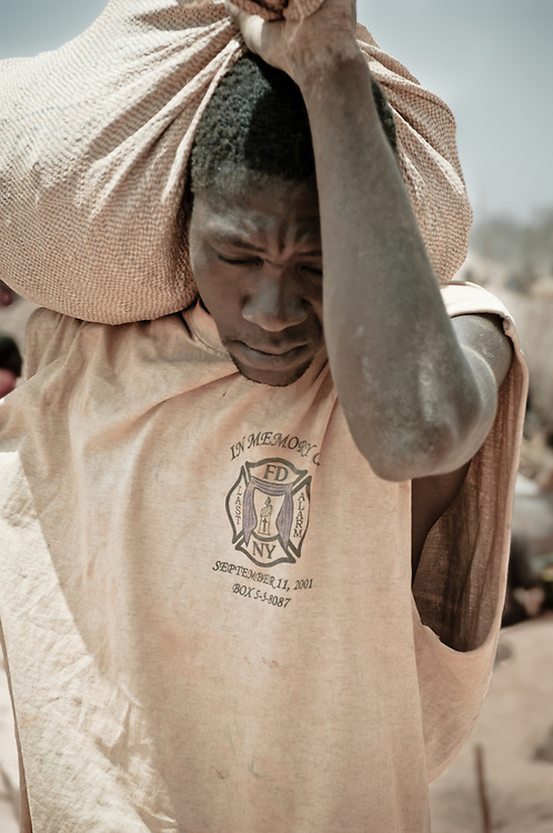 Stock photograph of an African gold miner carrying a bag of high grade gold ore at a local gold rush in Burkina Faso.