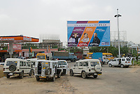 New Delhi's new CBD, Gurgaon is located an hour South of the city. SUVs near a Indian Oil gas station.
