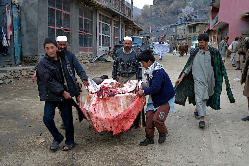 In the mining towns of the Panshir mountains life starts very early. Between 5 and 6am animals are butcherd and the meat transported to the butchers roadside stalls. Other shops selling warm clothing, boots, hunting rifles and general supplies also spread their wears on the roadside to attract custom. Khenj, Panshir Mountains, Afghanistan on the 19th of April 2009.