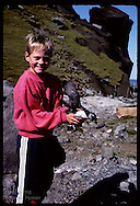 Kjartan Olafsson carries puffin chick he is about to release to sea @ Heimaey shore; Westmann Is Iceland