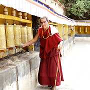 Elderly Tibetan Monk chanting along the outer wall prayer wheels at the Potala Palace.