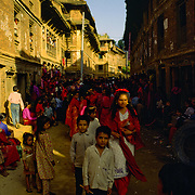 Nepali women - dressed in red - and their children celebrate the Newar Hindu festival of Tij, a celebration of women, in the ancient city of Bhaktapur, Kathmandu Valley, Nepal.