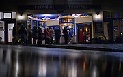 People line up in the evening rain to attend an old movie at the 100-year-old Patricia Theatre in Powell River, BC. (2013)