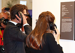 Image licensed to i-Images Picture Agency. 12/06/2014. Angelina Jolie and Brad Pitt put on headphones as they tour an art exhibition  on day three of the End Sexual Violence in Conflict  Global Summit in London.  Picture by Stephen Lock / i-Images