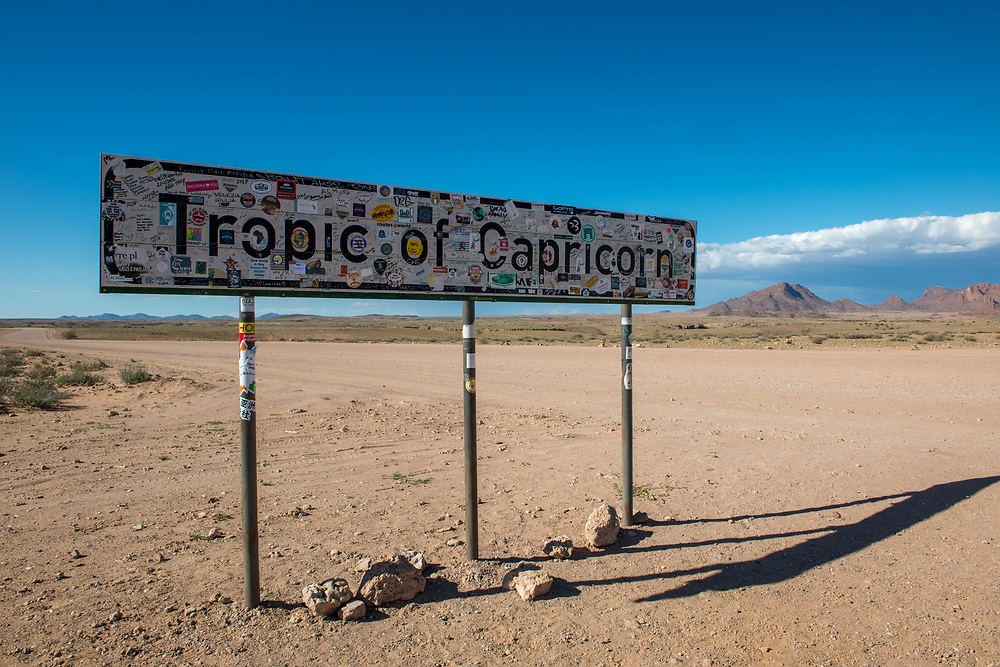 Tropic of Capricorn sign in the Namib desert, located in Namibia, Africa. The Tropic of Capricorn is part of a world map that indicates the division between the southern temperate zone and northern tropics.