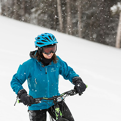 A woman fat tire biking on a snowy winter day in New Hampshire's White Mountains.