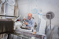 SIRACUSA, ITALY - 8 NOVEMBER 2016: Roberto Gibilisco (60)  cuts the marble that will be used for the gravestone of Musaab Shabani, a victim of the August 24th 2014 shipwreck, here at the Gibilisco marble-worker's workshop in Siracusa, Italy, on November 8th 2016.<br /> <br /> Musaab Shabani was buried in the cemetery of Sortino, marked by a gravestone with the number nine because at the time he hadn't been identified yet. He was later identified by his brother Abd thanks to the efforts of policeman Angelo Milazzo. Since then, Abd has arranged to have a gravestone made bearing his brother's name and date and place of birth as well as a religious inscription in Arabic, bringing a final bit of closure to this tragic chapter. <br /> <br /> On August 24th 2014, a boat carrying more than 400 migrants, departed from the coasts of Libya in the attempt to reach Italy, capsized in international waters in the Mediterranean Sea. Rescuers of the Italian Navy saved 352 people, and recovered 24 lifeless bodies.<br /> <br /> Following the events of the Arab Spring in 2011, including Gaddafi's death and Libya's plunge towards chaos, clandestine crossings skyrocketed, as did the number of people drowning. In 2014 over 170,000 arrived in Italy and since then more than 10,000 perished in the Mediterranean sea.<br /> <br /> Only a fraction of these bodies have ever been recovered, and, of the ones that have, the majority remain unidentified. In Sicily alone there are more than 1,500 graves of anonymous refugees and migrants–people from Syria and other war torn countries–who have drowned in shipwrecks at sea.<br /> <br /> Despite the decades long persistence of the problem, Italy has yet to develop a comprehensive approach to handling the bodies of shipwreck victims. Many pieces of a functional body identification system are in place, but its overall effectiveness is crippled by a lack of coordination between the various local agencies involved and national authorities.