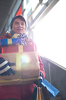 Low angle view of man holding gifts by window