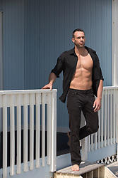 muscular man with an open shirt exposing his abs and hot muscle body on a deck