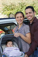 Portrait of couple with baby (1-6 months) in carrier by car