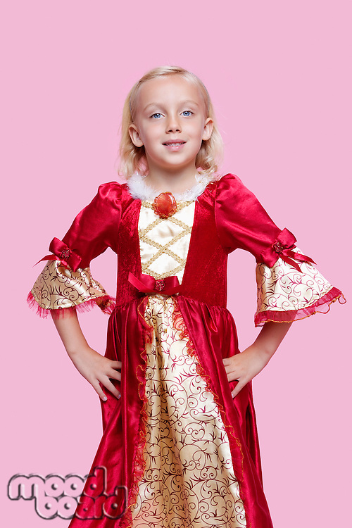 Portrait of a happy young girl dressed in princess costume over pink background