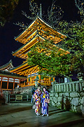 "Two women in kimonos consult smartphones under the three-storied Koyasu Pagoda which is lit at night. Kiyomizu-dera (""Pure Water Temple"") is an independent Buddhist temple in eastern Kyoto, Japan. Otowa-san Kiyomizu-dera temple is part of the Historic Monuments of Ancient Kyoto (Kyoto, Uji and Otsu Cities) UNESCO World Heritage site. Kiyomizu-dera was founded on the site of the Otowa Waterfall in the early Heian period, in 780 by Sakanoue no Tamuramaro. Ordered by Tokugawa Iemitsu, its present buildings were built entirely without nails in 1633."