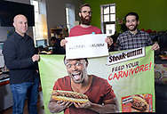 From left, Jesse Bender, Account Manager, From left, Nathan Allebach, Social Media Manager, and Christian Betlyon, Digital Strategist hold a Steak-umm marketing piece and a #verifysteakumm sign at Allebach Communications Tuesday December 19, 2017 in Souderton, Pennsylvania. The Montgomery County marketing firm is trying to have the Steam Twitter account verified with viral success. (WILLIAM THOMAS CAIN / For The Philadelphia Inquirer)
