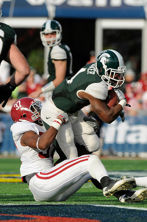 January 1, 2011: Edwin Baker of the Michigan State Spartans is tackled by Robert Lester of the Alabama Crimson Tide during the NCAA football game between the Michigan State Spartans and the Alabama Crimson Tide at the 2011 Capital One Bowl in Orlando, Florida. Alabama defeated MSU 49-7.