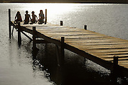 Four children (7-9) sitting on dock by lake back view.